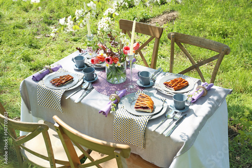 Aluminium Prints Picnic Table setting and cage with flowers in garden