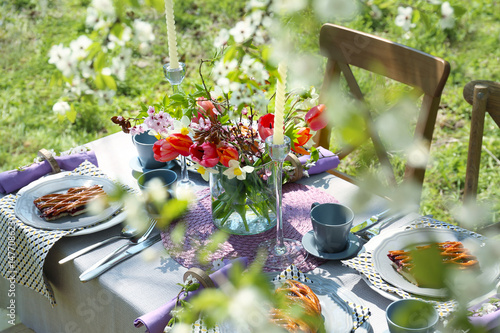 Keuken foto achterwand Picknick Table setting and cage with flowers in garden