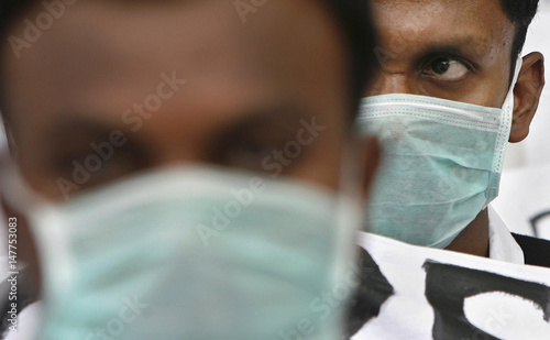 Foreign Medical Graduates (FMG) wearing masks attend a sit