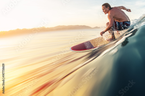 Valokuva  Surfer rides the perfect ocean wave at sunrise