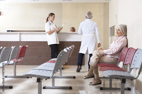Fotografie, Obraz  Doctors and patient discussing in hospital waiting room