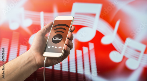 Fotobehang Muziekwinkel Close up of a man holding smartphone in hand and listening to music with mobile app. Red blurred note background. Modern online music streaming concept with free copy space for text.