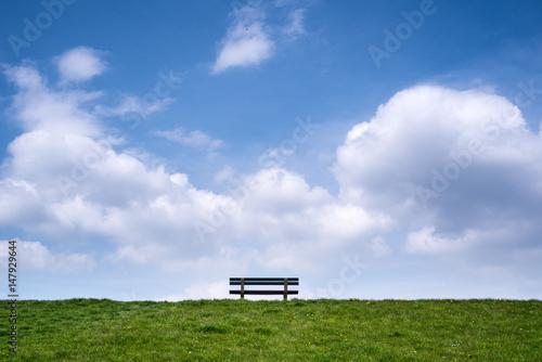 Foto Einsame Bank mit grüner Wiese und Blick auf endlosen Himmel mit Wolken an einem