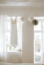 Wedding Dress Hanging In Front Of A Window