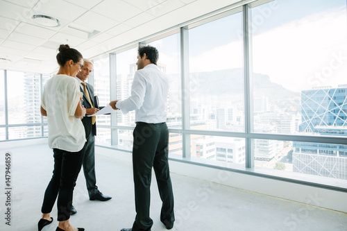 Real estate agent talking with potential clients at new office s Wallpaper Mural