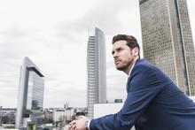 Businessman In Front Of Skyscrapers, Looking Pensive