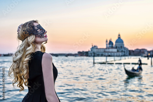 Spoed Foto op Canvas Gondolas Portrait of a woman with a mysterious look at sunset in Venice. Girl wearing a black mask and a gondola on Grand Canal background, Italy