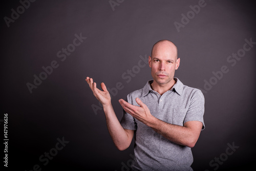 Valokuva  Mann mit grauem Poloshirt präsentiert etwas mit offenen Handflächen, herausforde