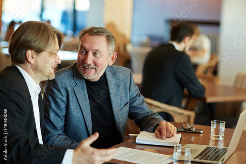Fototapety, obrazy: Two bearded white collar workers distracted from project discussion and chatting animatedly while sitting in cozy coffeehouse, waist-up portrait