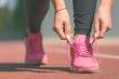 Running shoes - closeup of woman tying shoe laces. Female sport fitness runner getting ready for jogging outdoors on running track.