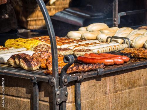 Poster Grill / Barbecue die Grillsaison startet: Bratwürste, Krakauer, Steak und Grillfackel auf dem Grill