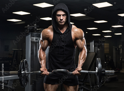 Brutal strong athletic men pumping up muscles workout