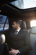 Portrait of successful Middle-Eastern businessman looking out of window of expensive luxury car