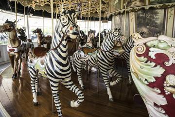 Fototapeta na wymiar Vintage restored carousel hand carved wooden zebras on a merry go round ride
