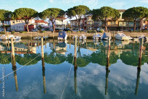 Fotobehang Stad aan het water Canal and boats in Grado in bright morning light. North-Eastern Italy, Europe.