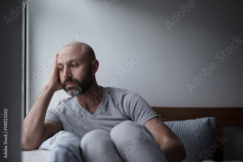 Photo  Mid forties depressed man in bed at home