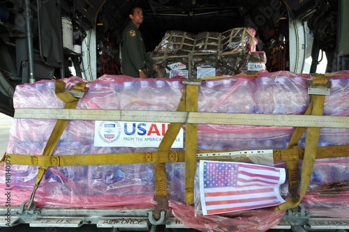 U S  military personnel loads aid supplies into a military transport