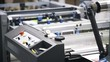 Close up of an industrial printer working at a printing plant. Locked down real time close up shot