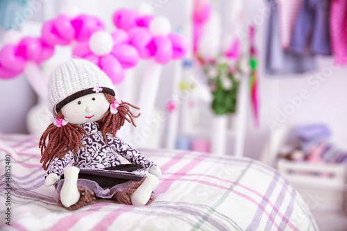 Obraz na plátne Cute doll on bed against blurred background