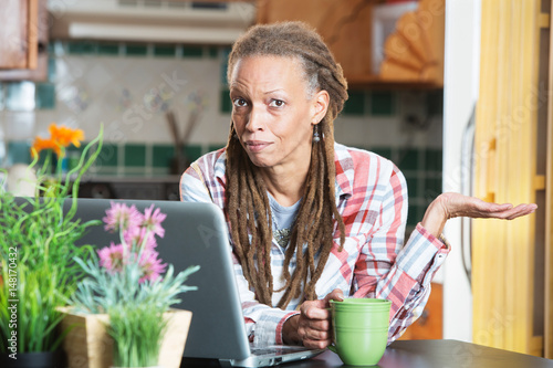 Fotografering  Unimpressed woman in kitchen with compute