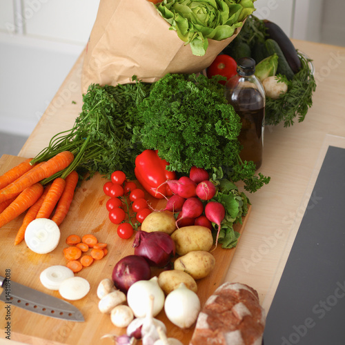 Tuinposter Groenten Grocery shopping bag with vegetables on kitchen