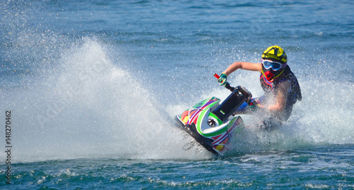 Poster Nautique motorise Jet Ski competitor cornering at speed creating at lot of spray.