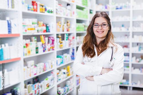 Fotografia  Pharmacist chemist woman standing in pharmacy - drugstore