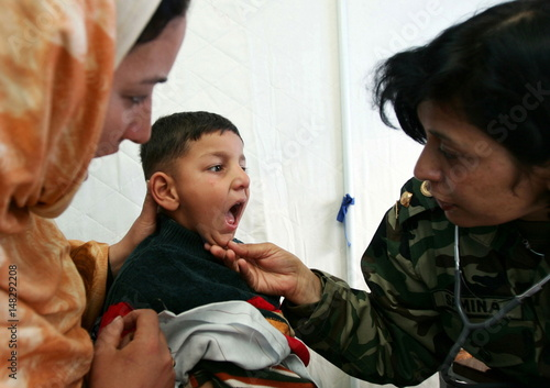 Pakistan's Army doctor Samina Azaz examines a Kashmiri boy