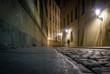 A motion blurred woman walks down a cobbled street in Prague at night