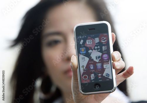 A woman shows her new iPhone which she bought from the black