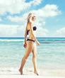 Beautiful, attractive woman in black bikini. Young and sporty girl posing on a beach at summer. Holiday, resort, tourism, concept.