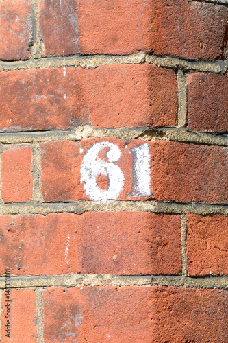 Fotografia  House number 61 painted sign