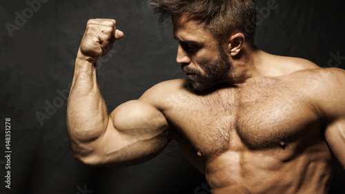 Fototapeta A muscular man flexing his biceps