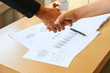 two business persons are doing hand check with sale report charts paper blur background