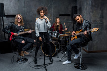Young Multiethnic Rock And Roll Band Rehearsing In Musical Studio