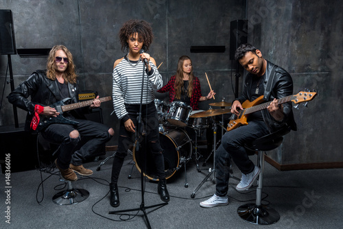 Fotografia Young multiethnic rock and roll band rehearsing in musical studio