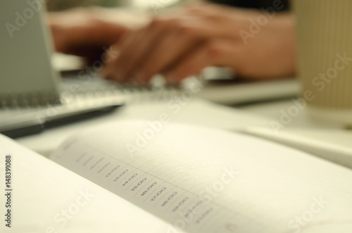 Open notepad with schedule on work-table and working man on