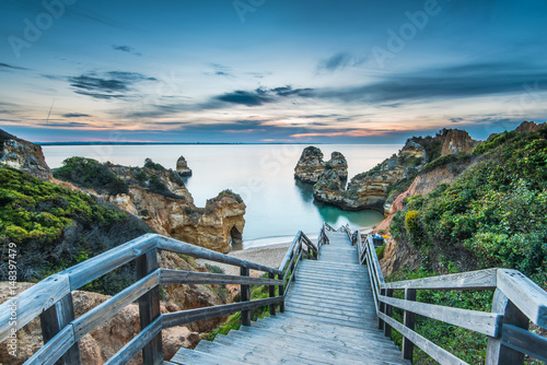Garden Poster Cappuccino Wooden footbridge walkway to beautiful beach Praia do Camilo on coast of Algarve region, Portugal
