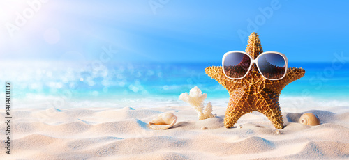Photo Starfish With Sunglasses On The Sunny Beach