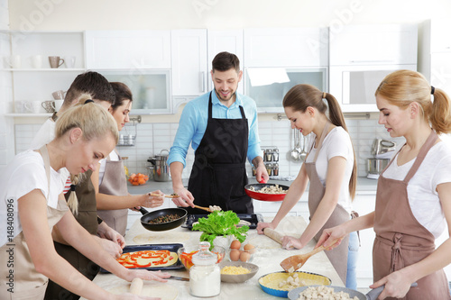Fotobehang Koken Male chef and group of people at cooking classes