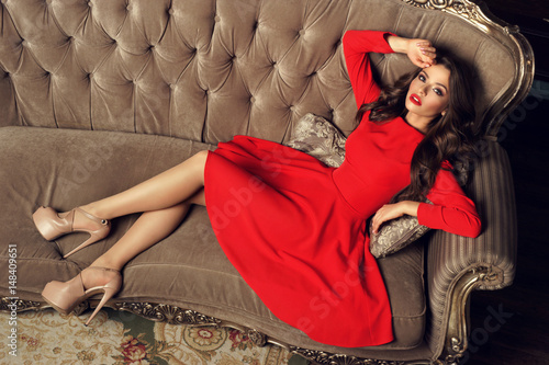 Fotografia  Sexy slim beautiful woman in red A-line dress lying on sofa in luxury interior and looking in camera