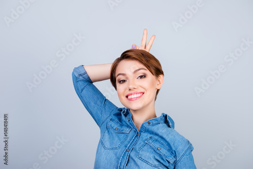 Playful Young Cute Girl Is Making Herself Horns With Fingers On