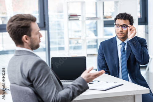 Fototapety, obrazy: Two businessmen in formal wear sitting and talking at job interview, business concept