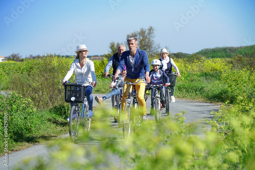 Family riding bikes together on country road