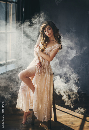 Fotografía  A young, beautiful woman sits near a window in a room with smoke