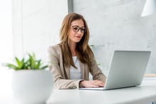 Beautiful Businesswoman Typing On Laptop