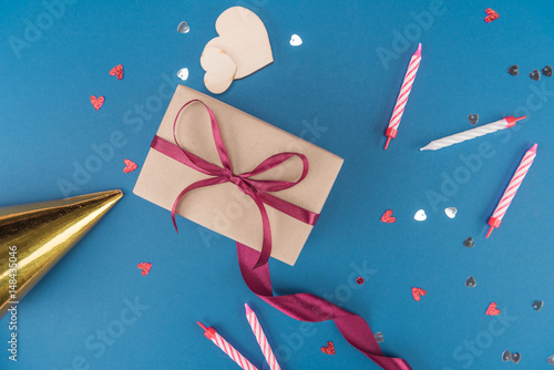 Top View Of Gift Box Birthday Hat And Candles Isolated On Blue