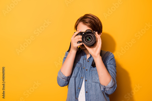 Fototapeta Close up photo of female photographer photographing with a camera in casual clot