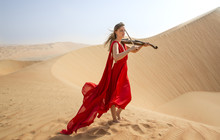 Woman In A Red Dress Playing A Violin In A Desert In Abu Dhabi