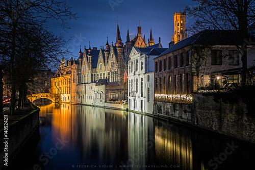 In de dag Brugge Night shot of historic medieval buildings along a canal in Bruges, Belgium